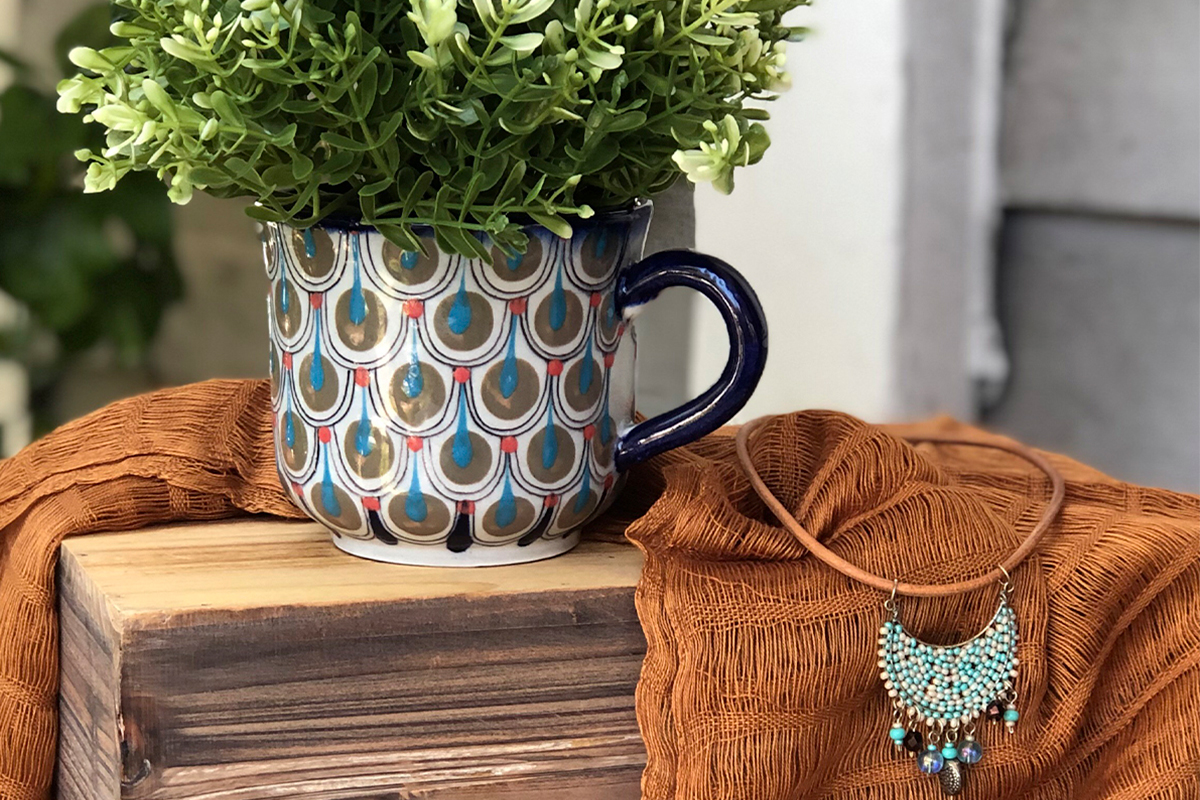 artsy mug with plant and necklace